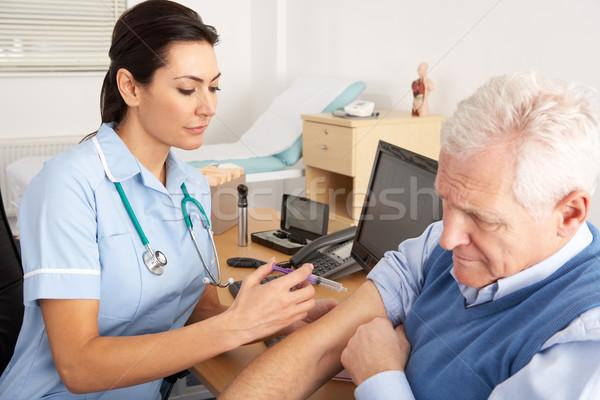 British nurse giving injection to senior man Stock photo © monkey_business
