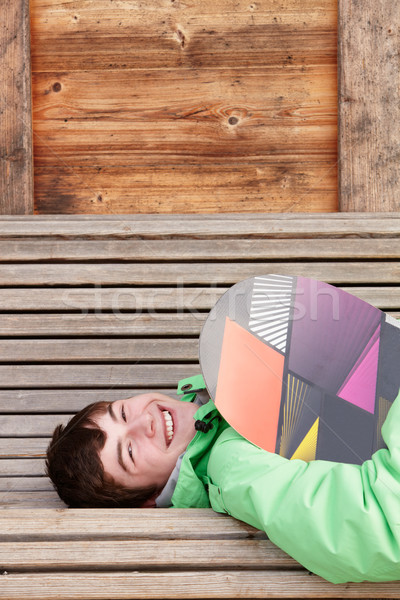 Teenage Boy With Snowboard On Ski Holiday Lying On Wooden Bench Stock photo © monkey_business