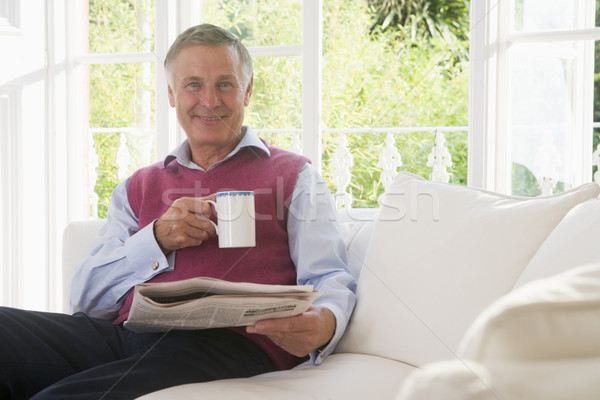Man in living room with coffee reading newspaper smiling Stock photo © monkey_business