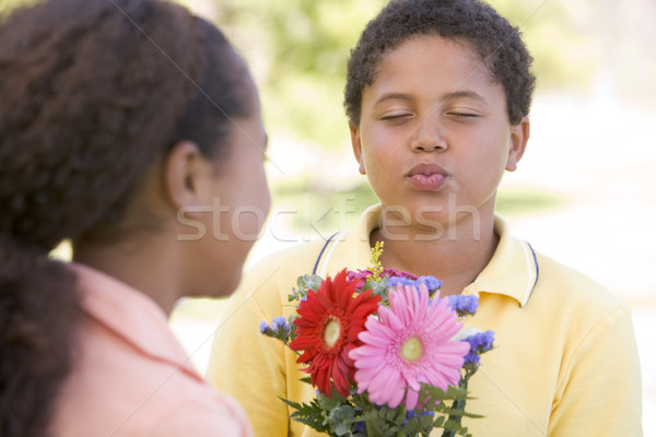 Young boy giving young girl flowers and puckering up Stock photo © monkey_business