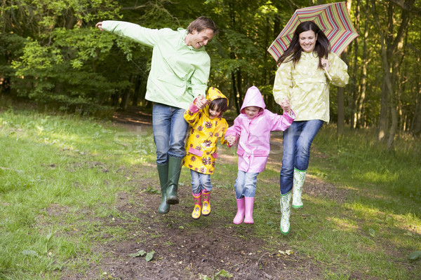 Family outdoors skipping with umbrella smiling Stock photo © monkey_business