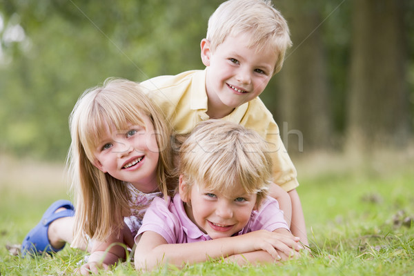 Stock photo: Three young children playing outdoors smiling