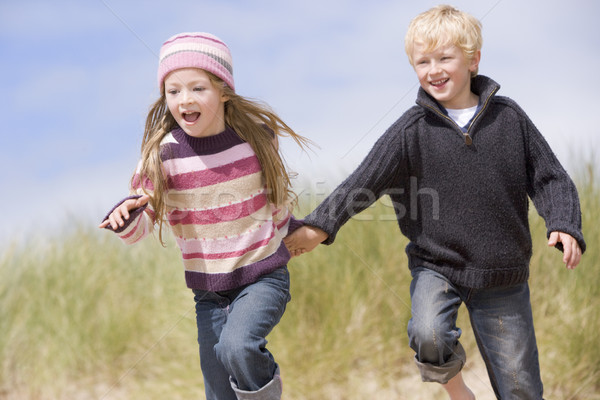 Two young children running on beach holding hands smiling Stock photo © monkey_business