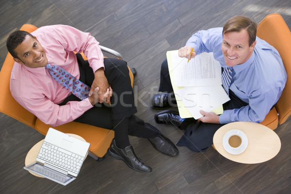 Two businessmen sitting indoors with coffee laptop and folder sm Stock photo © monkey_business