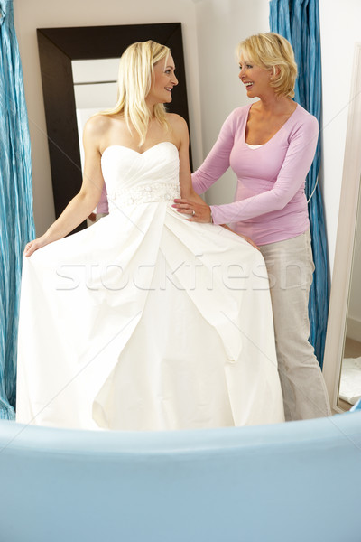 Bride trying on wedding dress with sales assistant Stock photo © monkey_business