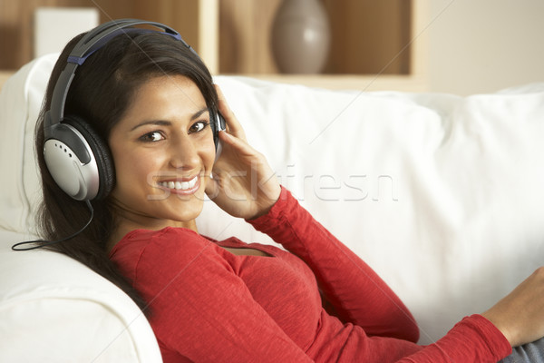 Stock photo: Young Woman Listening To Music At Home