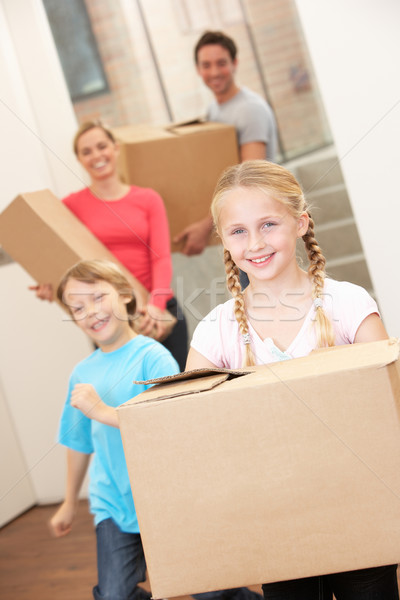 Family happy on moving day carrying cardboard boxes Stock photo © monkey_business