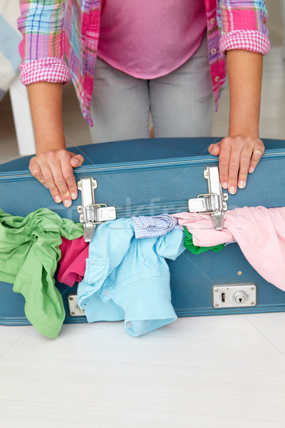 Teenage girl struggling to close suitcase Stock photo © monkey_business