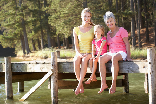 Mother,daughter and grandmother sitting by lake Stock photo © monkey_business