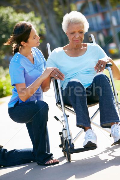 Cuidador empujando infeliz altos mujer silla de ruedas Foto stock © monkey_business