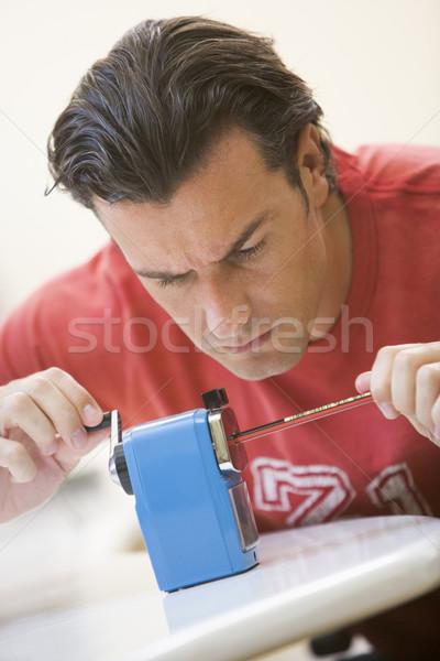 Man indoors using pencil sharpener Stock photo © monkey_business
