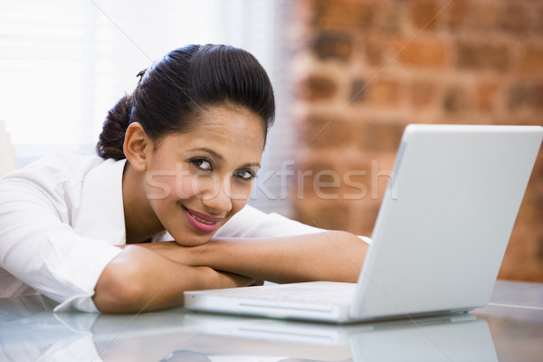 Businesswoman in office with laptop smiling Stock photo © monkey_business