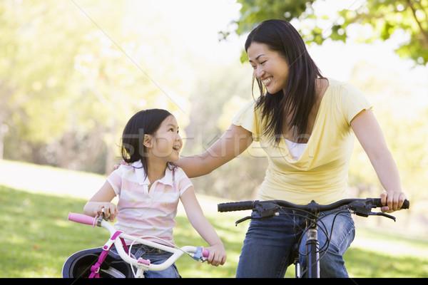 Сток-фото: женщину · велосипедах · улице · улыбающаяся · женщина · улыбаясь