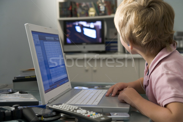 Young boy in bedroom using laptop and listening to MP3 player Stock photo © monkey_business