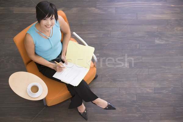 Businesswoman sitting indoors with coffee and folder smiling Stock photo © monkey_business
