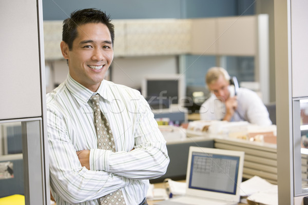 Businessman standing in cubicle smiling Stock photo © monkey_business