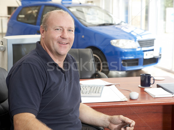 Car salesman sitting in showroom smiling Stock photo © monkey_business