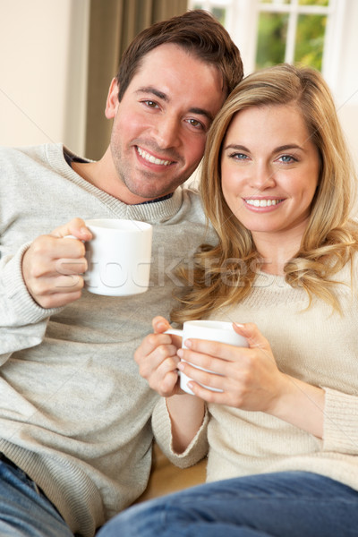 Stock photo: Young couple sitting and relaxing on sofa with cup in hand