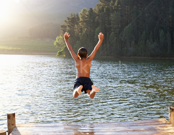 Stock photo: Young boy jumping into lake