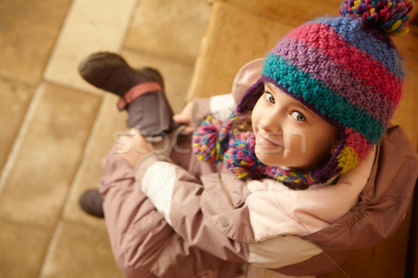 Young Girl Sitting On Wooden Seat Putting On Warm Outdoor Clothe Stock photo © monkey_business