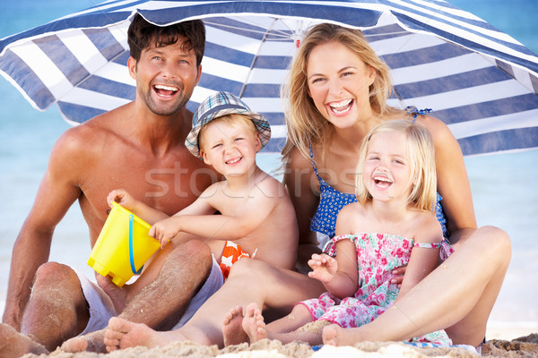 Family Sheltering From Sun Under Beach Umbrella Stock photo © monkey_business