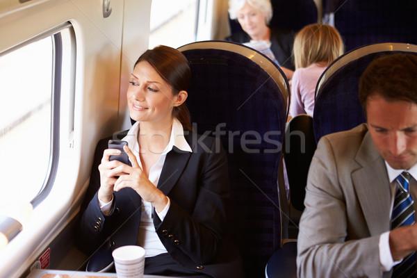 üzletasszony ingázás munka vonat mobiltelefon nő Stock fotó © monkey_business