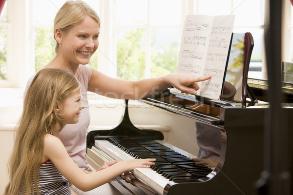 Woman and young girl playing piano and smiling Stock photo © monkey_business