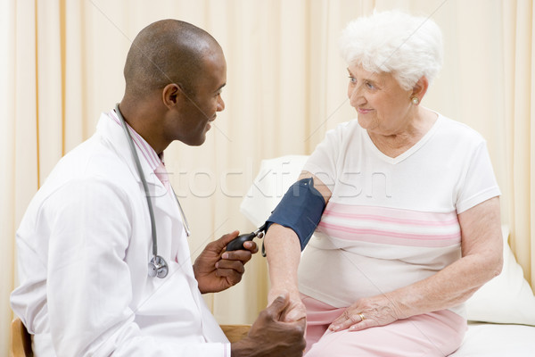 Doctor checking woman's blood pressure in exam room smiling Stock photo © monkey_business