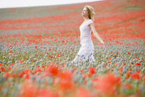 Woman walking in poppy field smiling Stock photo © monkey_business