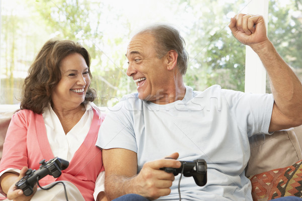 Stock photo: Senior Couple Playing Computer Game At Home