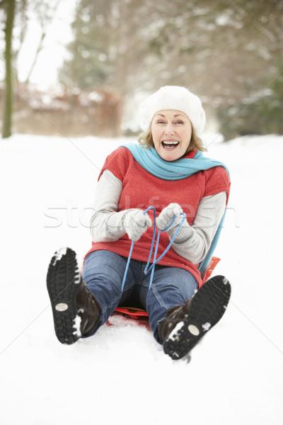 Senior Woman Sledging Through Snowy Woodland Stock photo © monkey_business