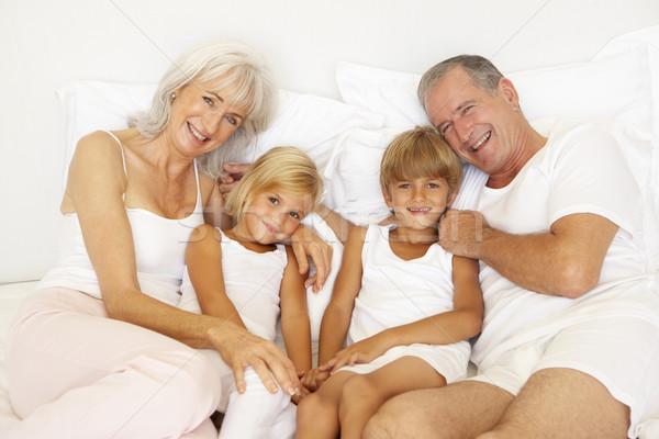 Grootouders ontspannen bed kleinkinderen vrouw gelukkig Stockfoto © monkey_business