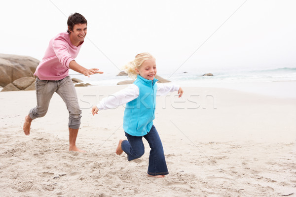 Father Chasing Daughter Along Winter Beach Stock photo © monkey_business