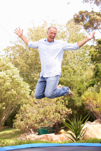 Middle Aged Man Jumping On Trampoline In Garden Stock photo © monkey_business