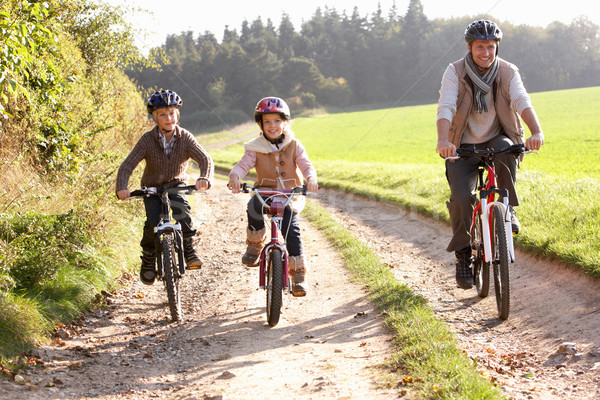 Young father with children ride bikes in park Stock photo © monkey_business