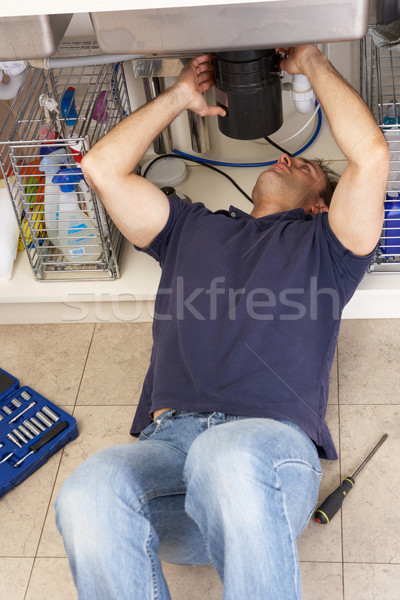 Stock photo: Plumber Working On Sink In Kitchen