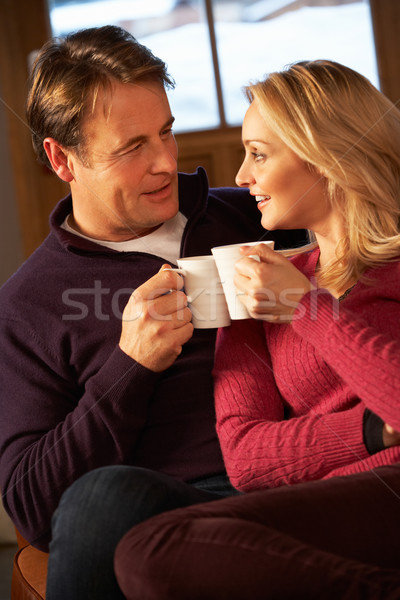 Middle Aged Couple Sitting On Sofa With Hot Drinks Stock photo © monkey_business