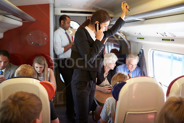 Businesswoman Using Mobile Phone On Busy Commuter Train Stock photo © monkey_business