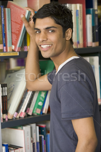 Male college student reaching for a library book Stock photo © monkey_business