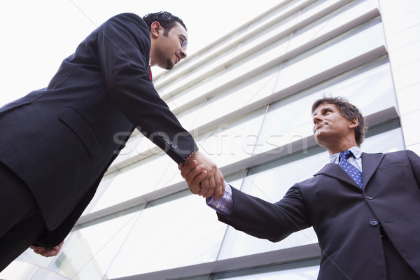 Stock photo: Businessmen shaking hands outside office building