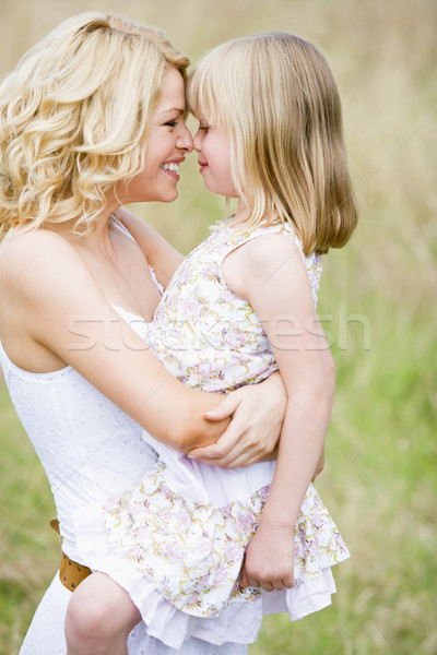 Stock photo: Mother holding daughter outdoors smiling