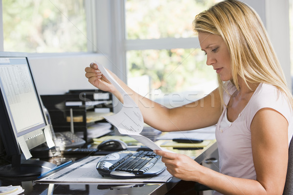 Stock photo: Woman in home office with computer and paperwork frowning