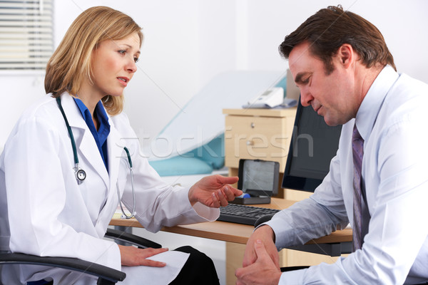 American doctor talking to depressed businessman Stock photo © monkey_business