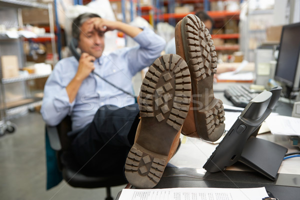 Stock photo: Businessman Putting Feet Up On Desk In Warehouse