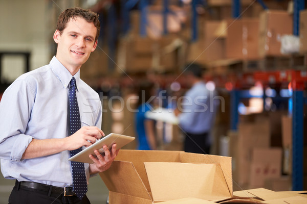 Manager In Warehouse Checking Boxes Using Digital Tablet Stock photo © monkey_business