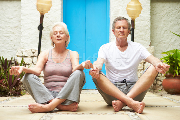 Senior Couple Meditating Outdoors At Health Spa Stock photo © monkey_business