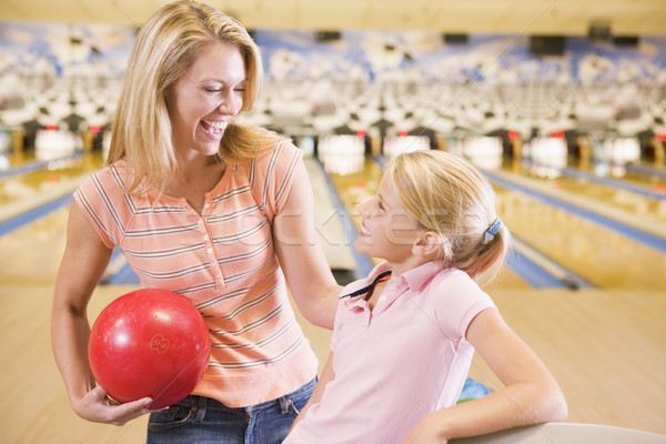 Woman and young girl in bowling alley holding ball and smiling Stock photo © monkey_business