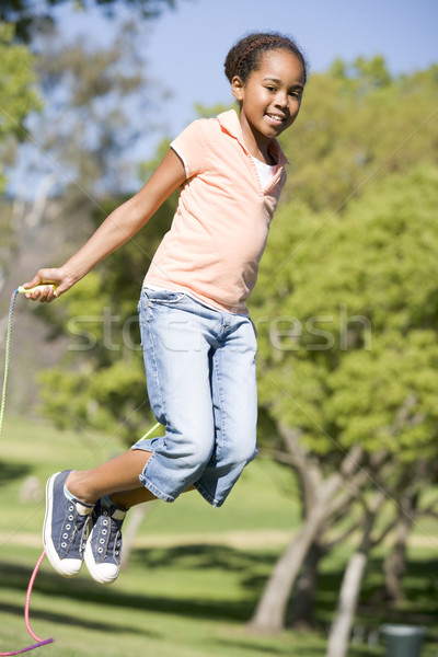 Young girl using skipping rope outdoors smiling Stock photo © monkey_business