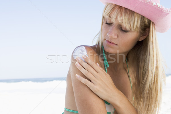 Młoda kobieta ochrona przed słońcem produktu kobieta plaży Zdjęcia stock © monkey_business
