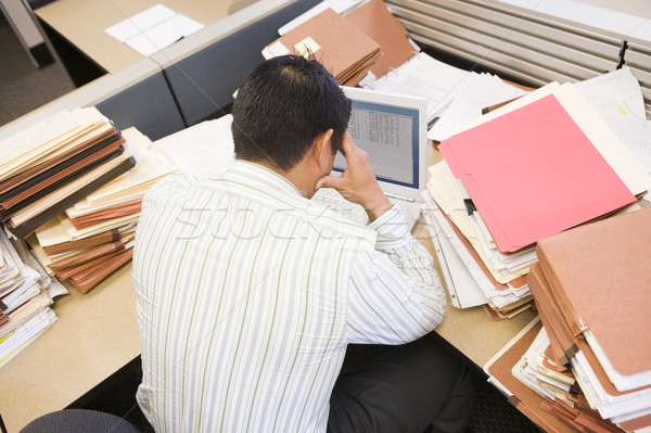 Businessman in cubicle with laptop and stacks of files Stock photo © monkey_business